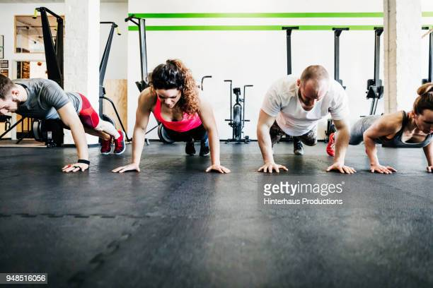 fitness enthusiasts doing pushups - small group of people stock pictures, royalty-free photos & images