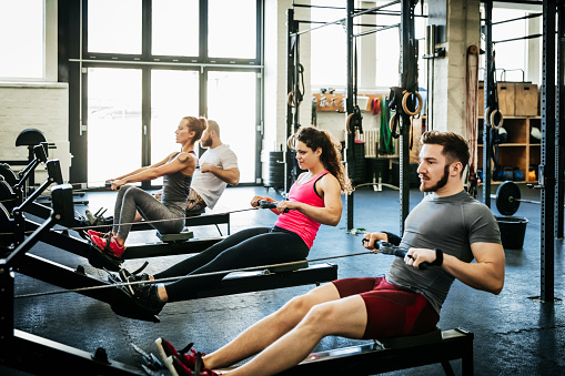 Fitness Enthusiasts Exercising Using Rowing Machines - gettyimageskorea