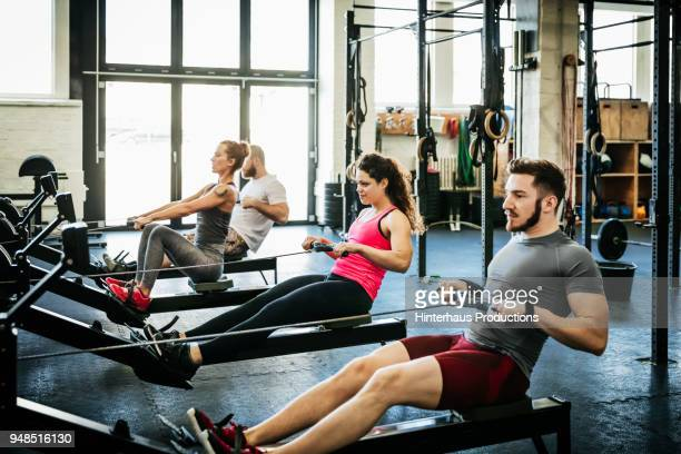 fitness enthusiasts exercising using rowing machines - dansstudio stock pictures, royalty-free photos & images