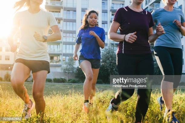 fitness enthusiasts jogging together outdoors - mid adult stock pictures, royalty-free photos & images