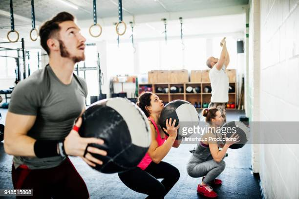 fitness enthusiasts keeping fit using weighted balls - sports training stock pictures, royalty-free photos & images