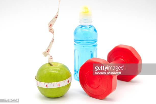 fitness equipment. healthy food. apple, dumbbells and measuring tape on white background. view from above - dumbbell stock pictures, royalty-free photos & images