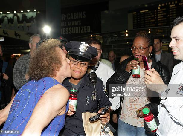 Fitness expert Richard Simmons kisses a Amtrak police officer in Penn Station at the Ocean Spray Cranergy Fuel Station Ocean Spray May 15 New York...