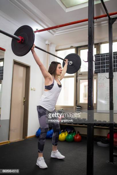 fitness female athlete lifting weights in gym - snatch weightlifting stock photos and pictures