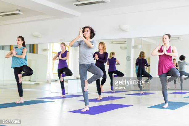 Fitness female group doing yoga in gym