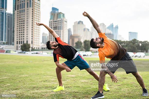 fitness friends doing stretching in dubai marina - membro parte do corpo - fotografias e filmes do acervo