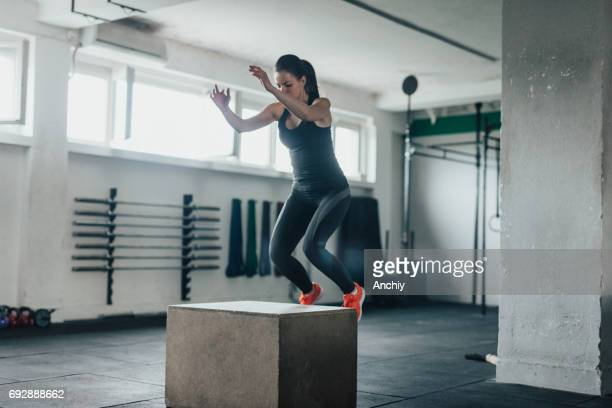 Fitness girl in mid-air doing box squats