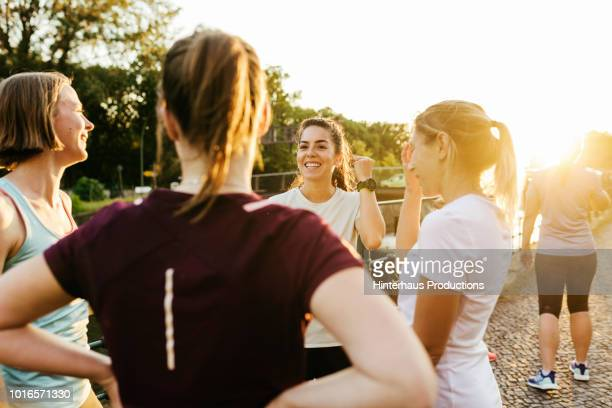 fitness group chatting before city run - pedal pushers stock pictures, royalty-free photos & images