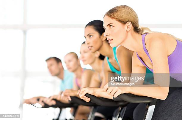 Fitness Group Exercising On Spin Bikes In Gym