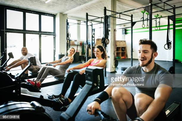 Fitness Group Exercising With Rowing Machines Together