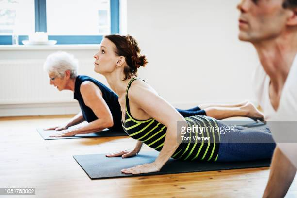 fitness group practicing yoga - acostado boca abajo fotografías e imágenes de stock