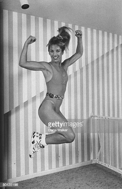 Fitness guru Denise Austin jumping posing midair during her routine on the top floor of her home