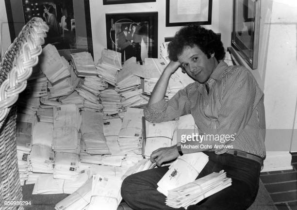 Fitness guru Richard Simmons poses for a portrait session with piles of fan mail at home in August 1980 in Los Angeles California