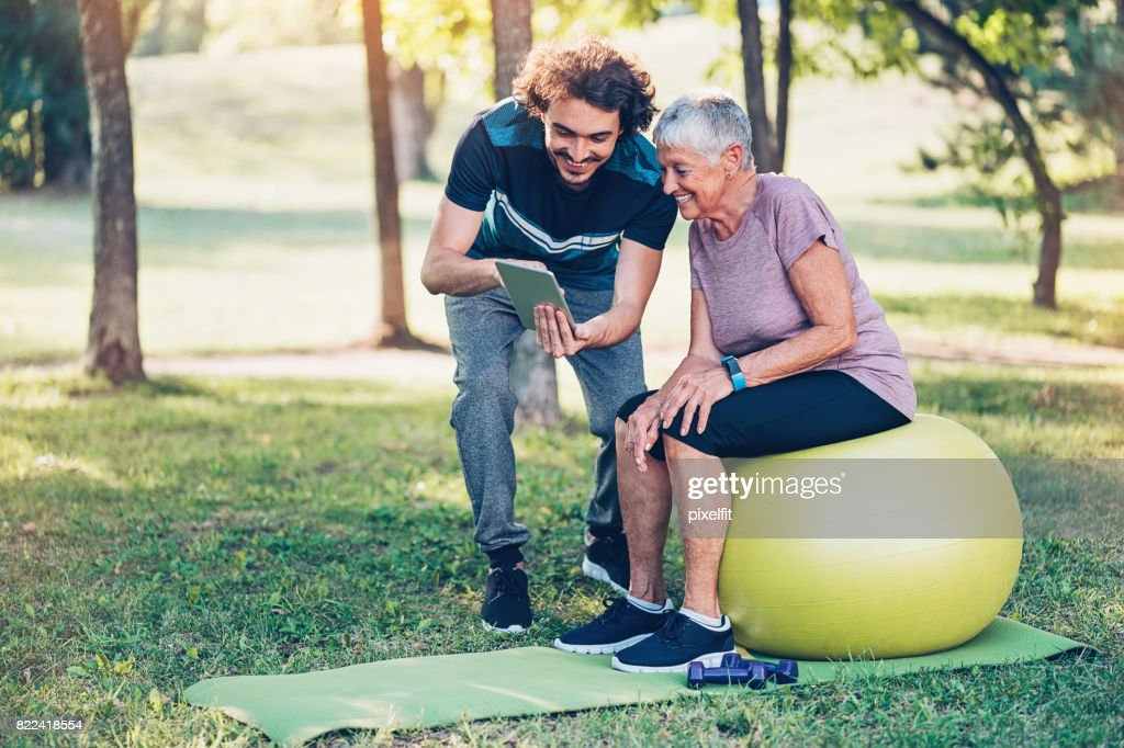 Fitness instructor and senior woman with digital tablet : Stock Photo