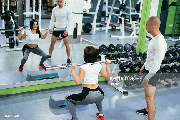Fitness instructor and trainee in gym