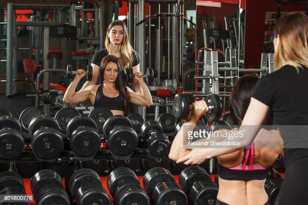 Fitness instructor assisting a woman doing training exercises