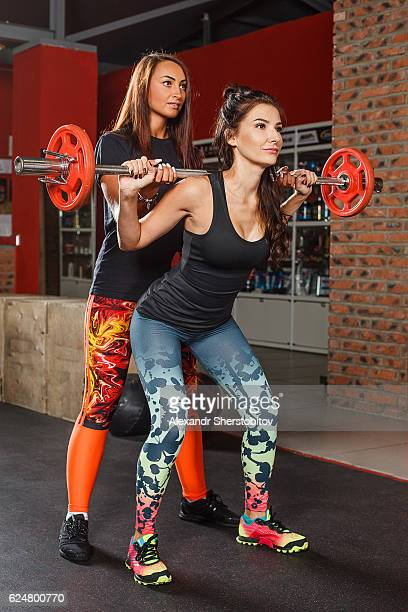 Fitness instructor assisting a woman doing training exercising