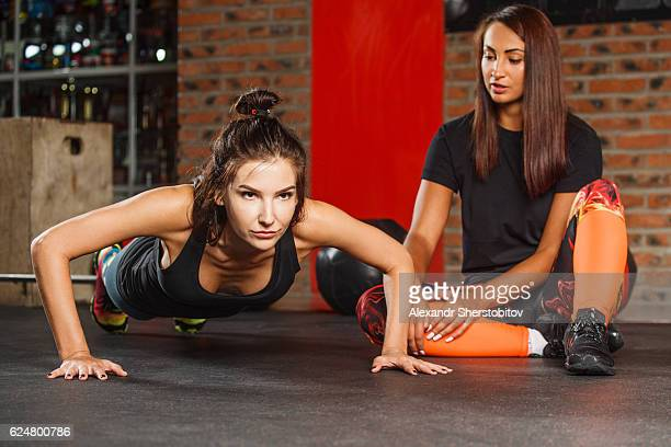 Fitness instructor assisting woman doing training exercises