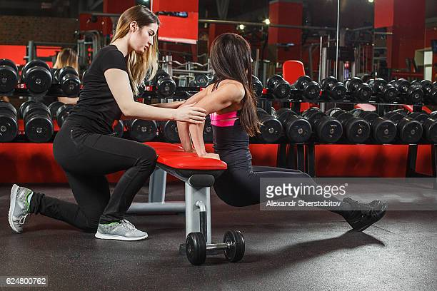 Fitness instructor assisting woman in gym