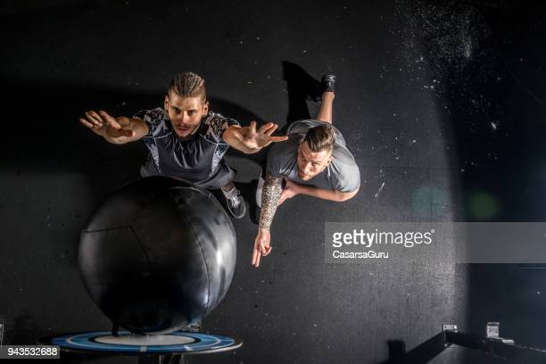 fitness instructor counting for young adult man during strength exercise - medicine ball stock pictures, royalty-free photos & images