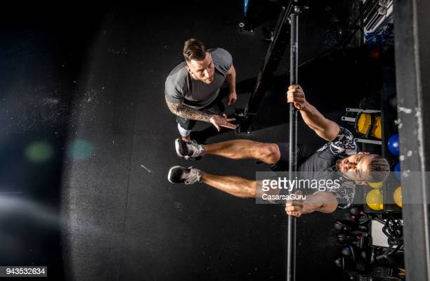 Fitness Instructor Counting for Young Man During Exercise