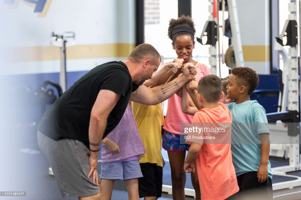 Fitness instructor encourages children in group exercise class : Stock Photo