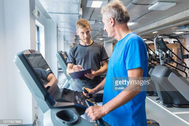 fitness instructor explaining training plan for senior in gym - drug rehab stock pictures, royalty-free photos & images