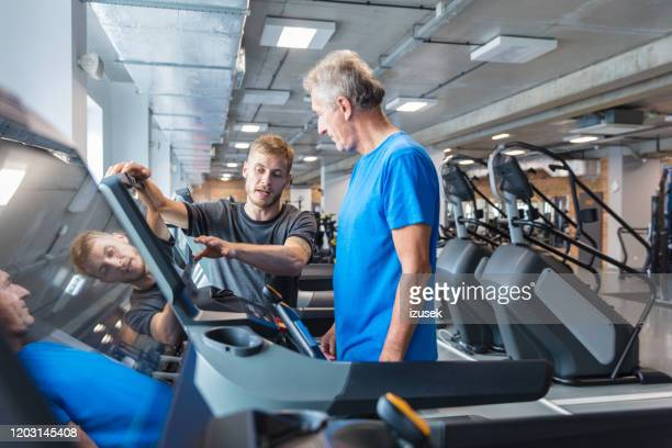 fitness instructor explaining training plan for senior in gym - leisure facilities stock pictures, royalty-free photos & images
