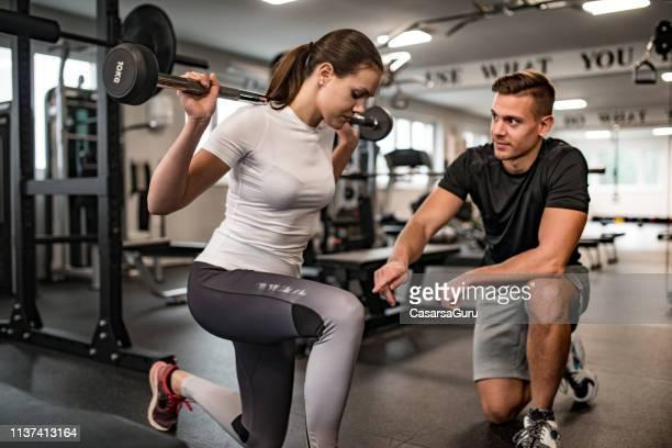 istruttore di fitness che guida la giovane donna quando esercita - allenatore foto e immagini stock