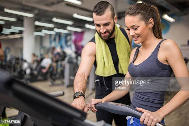 Fitness instructor helping a woman to adjust speed on treadmill.