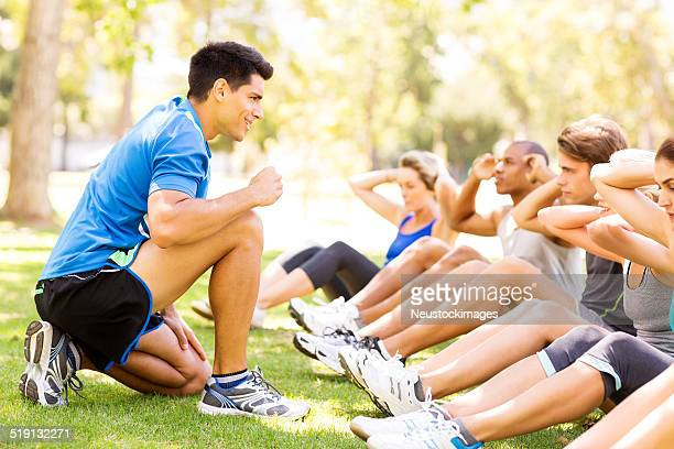 Fitness Instructor Motivating People In Doing Sit-Ups At Bootcamp