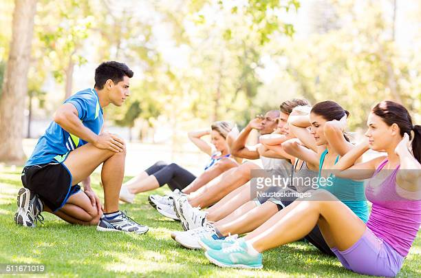 Fitness Instructor Motivating People In Doing Sit-Ups At Park