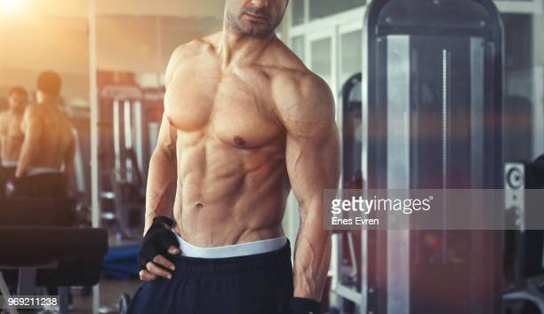 Fitness instructor posing in health club with dumbbell