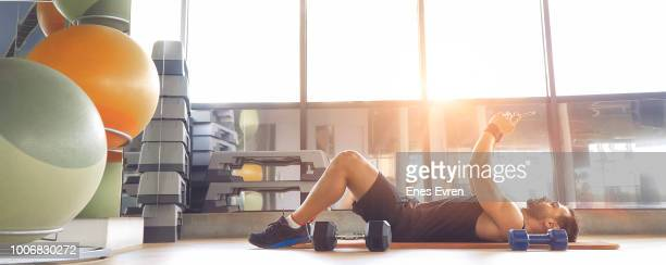 Fitness instructor taking selfie in health club with dumbbell