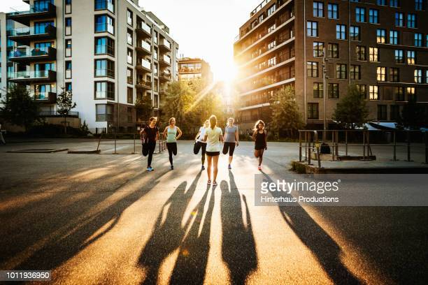 fitness instructor talking to class outdoors - sunlight stock-fotos und bilder
