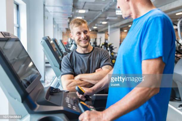 fitness instructor talking with senior man at rehab - drug rehab stock pictures, royalty-free photos & images