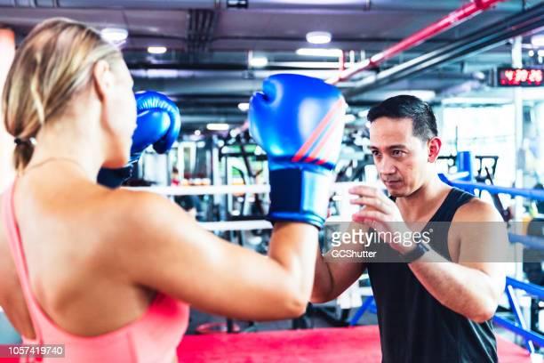 instructor de fitness entrenamiento a mujer en ring de boxeo - países del golfo fotografías e imágenes de stock