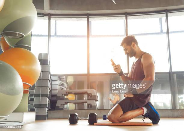Fitness instructor using mobile phone in health club with dumbbell