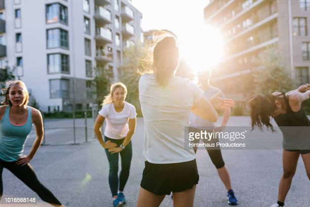 fitness instructor warming up with class outdoors - sports stock-fotos und bilder