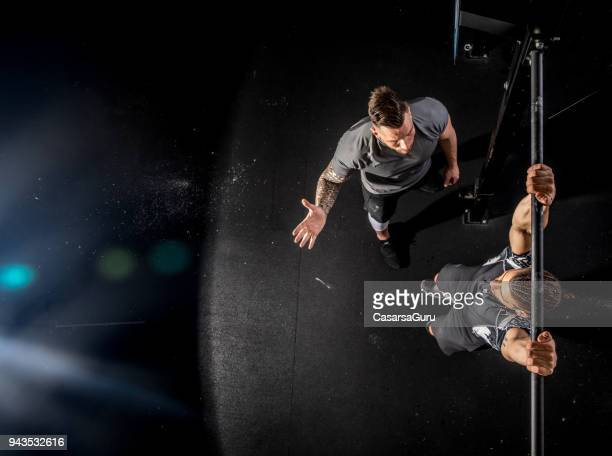 fitness instructor watching young man during exercise - crossfit stock pictures, royalty-free photos & images