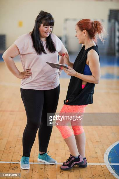 Fitness instructor with digital tablet talking with woman in gym