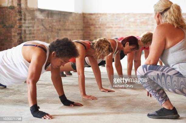 Fitness instructor working with a group who are in the plank position