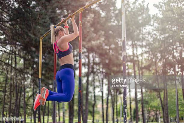 fitness instruktor doing pull up in local park - chin ups stock photos and pictures
