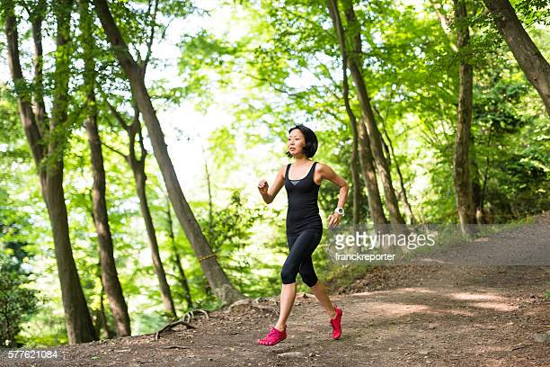 Fitness japanese woman running on the forest