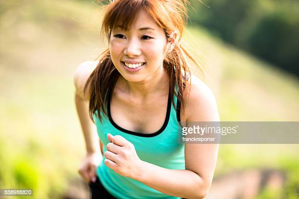 Fitness japanese woman running on the park