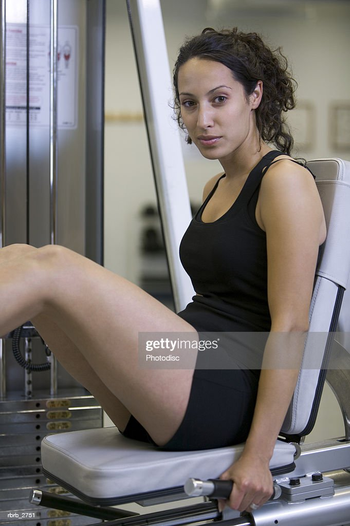 fitness lifestyle shot of a young adult woman as she sits at the leg press in the weight room : Foto de stock