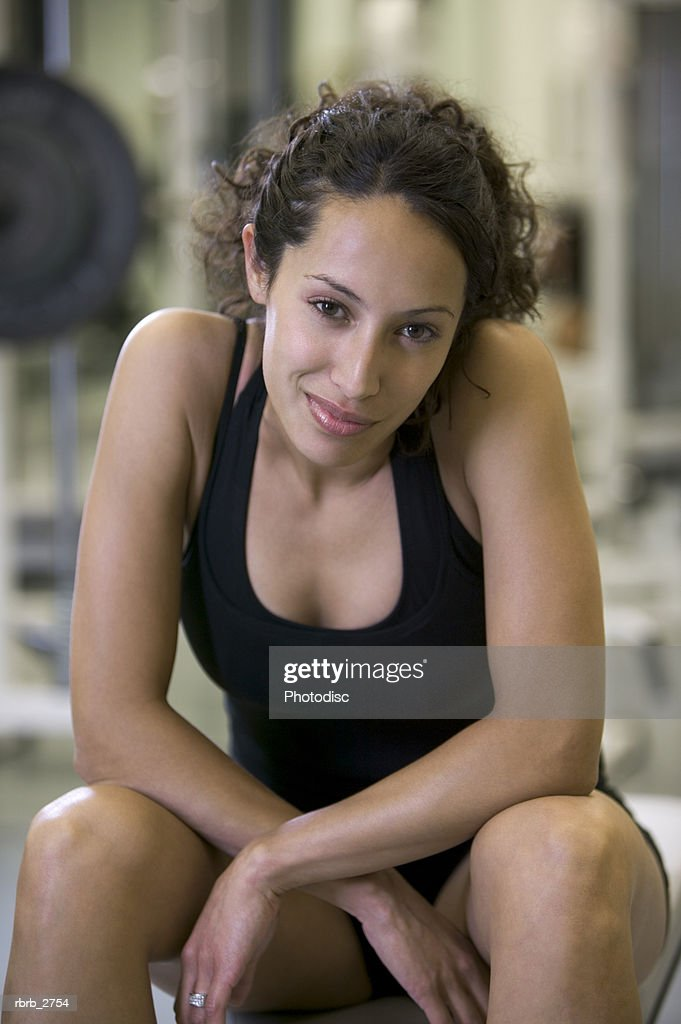 fitness lifestyle shot of a young adult woman in a workout outfit as she sits in a weight room : Foto de stock