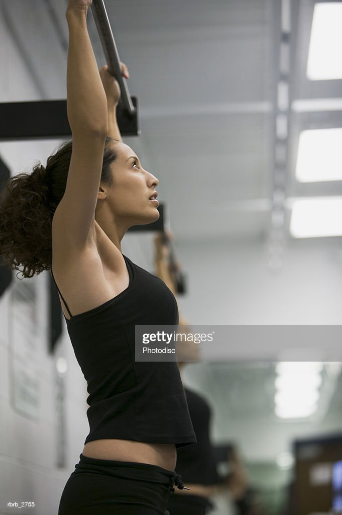 fitness lifestyle shot of a young adult woman in a workout outfit as she does pull ups : Foto de stock