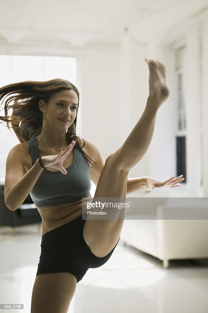 fitness lifestyle shot of an attractive young adult female in workout clothes as she kicks up into the air : Foto de stock