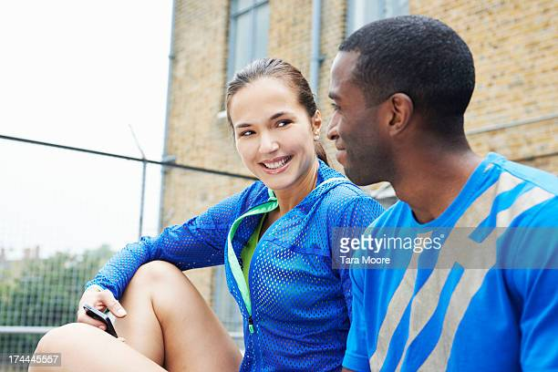 fitness man and woman talking with mobile phone